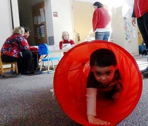 A young boy crawling through a red tube